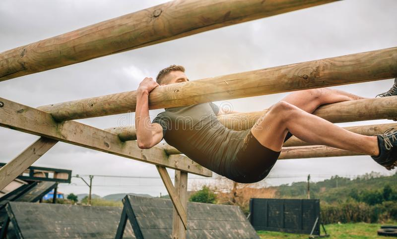 Participant in a obstacle course doing weaver. Male participant in a obstacle course doing weaver obstacle stock photo