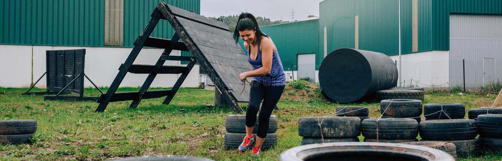 Participant in an obstacle course dragging wheels. Female participant in an obstacle course dragging wheels seen from behind stock photography
