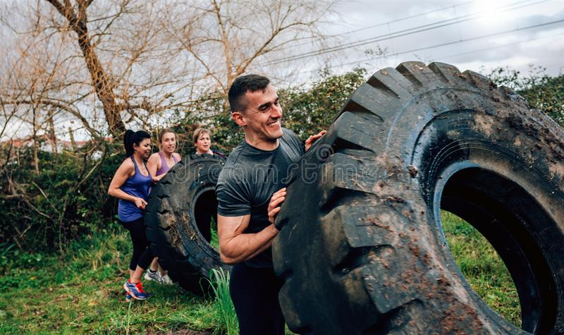 Participant in an obstacle course turning wheel. Male participant in an obstacle course turning truck wheel with partners in background stock images