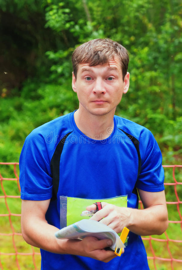 The participant of orienteering competitions. Holds a map in hands and reflects on a correct route of run royalty free stock photos