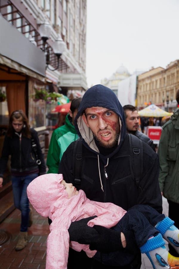 Participante con el bebé en el desfile del zombi imagen de archivo