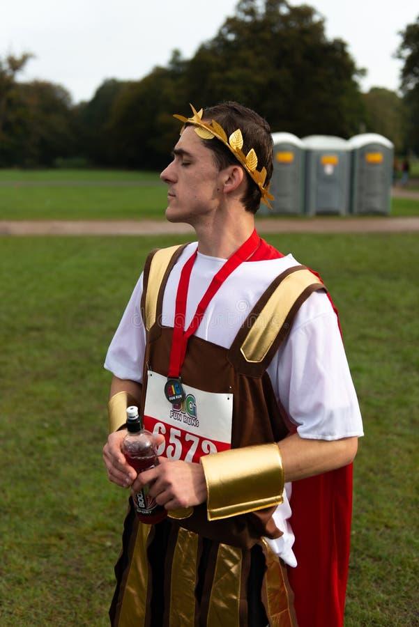 Participante del funcionamiento de la caridad vestido en la ropa romana imagen de archivo libre de regalías