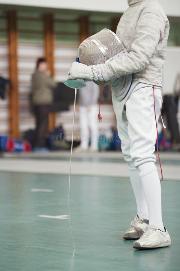 Participante del torneo de cercado con el estoque y de la máscara protectora en manos imagen de archivo