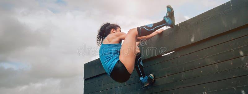 Participante na parede de escalada do curso de obstáculo fotografia de stock royalty free