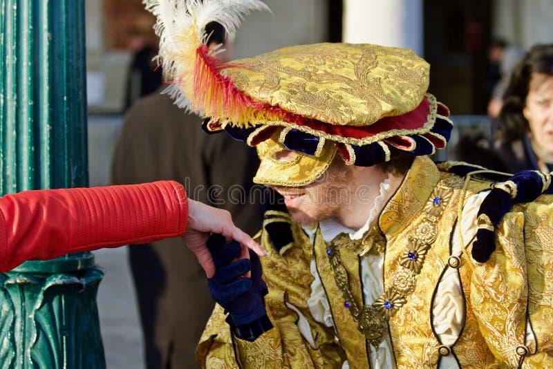 Participante y juerguista del carnaval de Venecia Mano de príncipe Charming Kissing imagenes de archivo