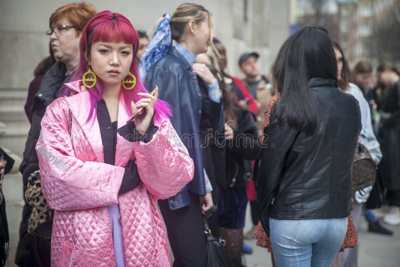 Participantes à moda que recolhem fora de 180 a costa para o London Fashion Week Uma menina com cabelo cor-de-rosa em saia-calças fotografia de stock royalty free