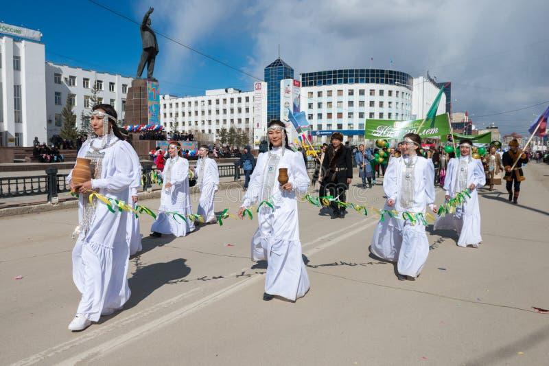 Participantes de la demostración del desfile - las muchachas yakutas en trajes nacionales están sosteniendo Sakha Choron imagenes de archivo