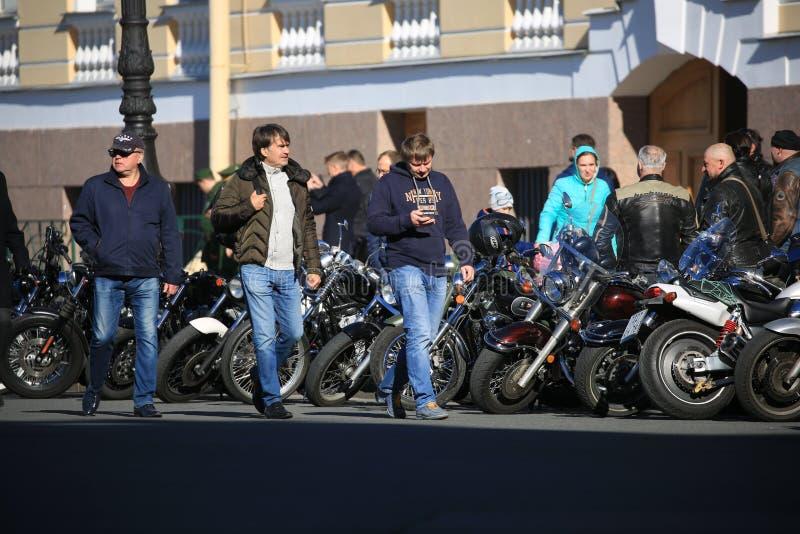 Participantes del movimiento del motorista de St Petersburg con sus motocicletas cerca de la pared del edificio del estado mayor  foto de archivo libre de regalías