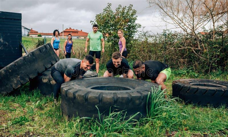 Participantes em um curso de obstáculo que gerencie uma roda fotos de stock