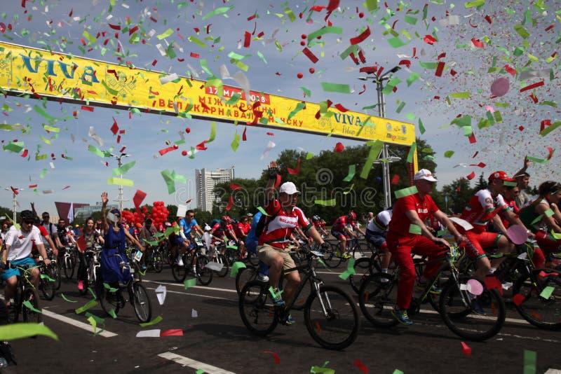 Participantes en el paseo anual del carnaval de los ciclistas a lo largo de la avenida de Pobediteley foto de archivo