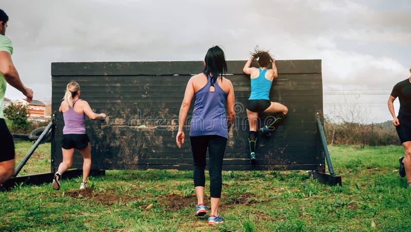 Participantes na parede de escalada do curso de obstáculo imagem de stock
