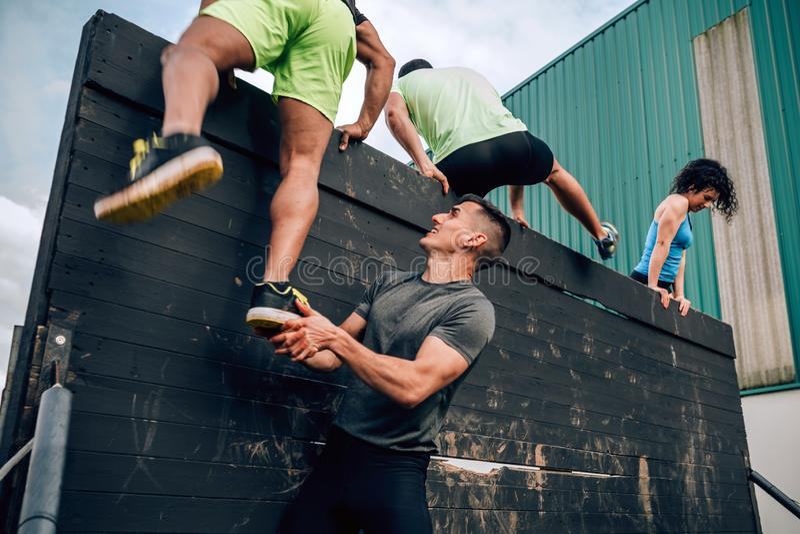 Participantes na parede de escalada do curso de obstáculo imagens de stock royalty free