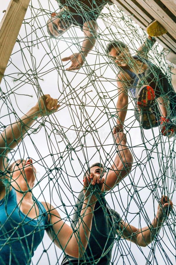 Participantes na rede de escalada do curso de obstáculo imagens de stock