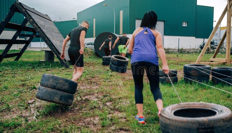 Participantes nas rodas de arrasto de um curso de obst?culo fotos de stock
