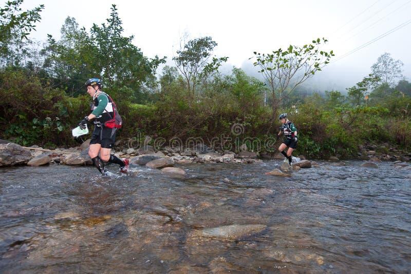 Participantes que vadeiam através do rio na raça imagem de stock royalty free