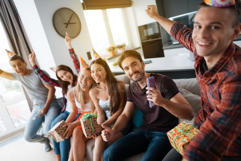 Participants in the birthday party make a group photo. They are sitting on a couch. stock photos