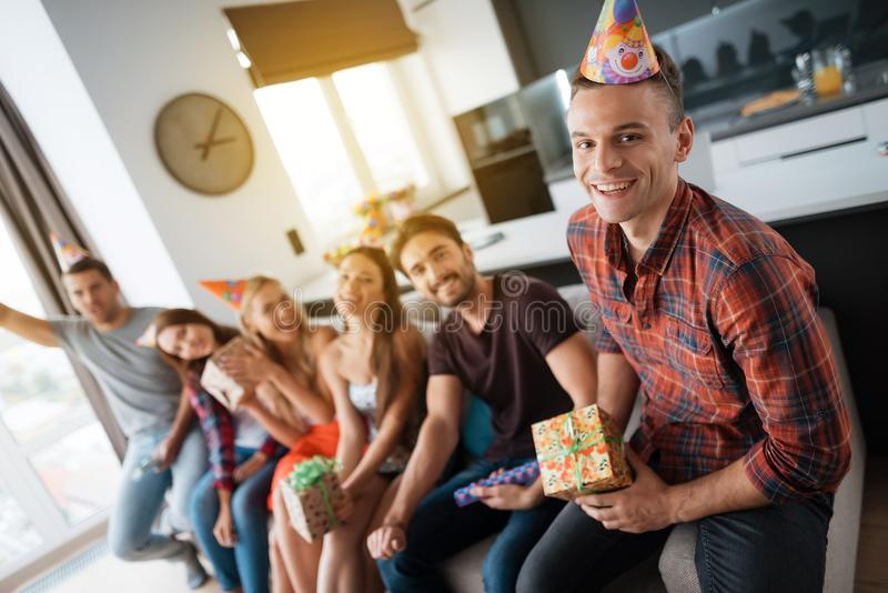 Participants in the birthday party make a group photo. They are sitting on a couch. royalty free stock image