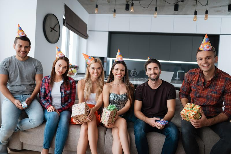 Participants in the birthday party make a group photo. They are sitting on a couch. royalty free stock photo