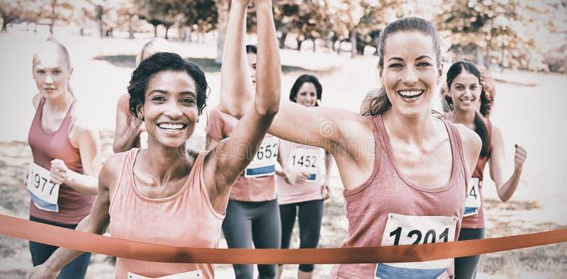 Participants de cancer du sein croisant la ligne d'arrivée à la course photo stock