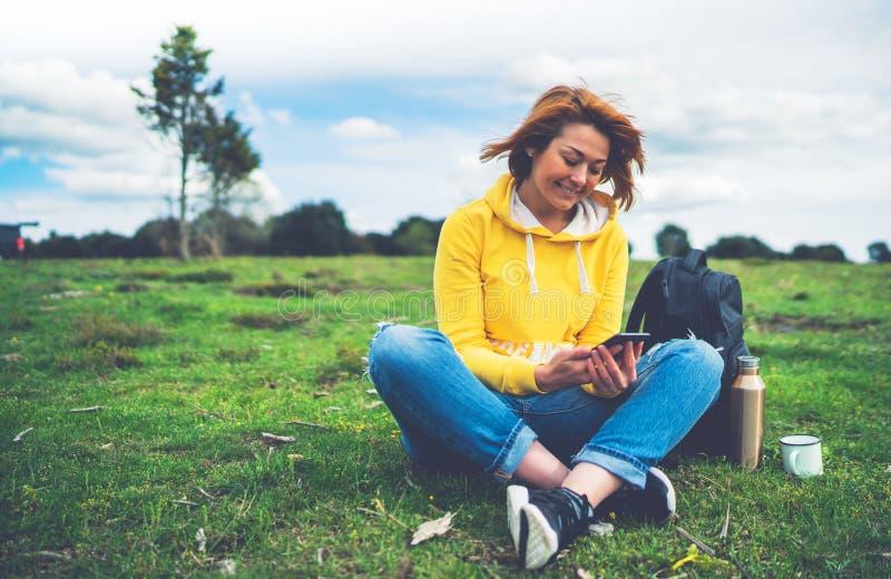 Participation de femme de sourire en technologie femelle d'instrument de mains, message textuel de touristes de jeune fille sur l photographie stock libre de droits