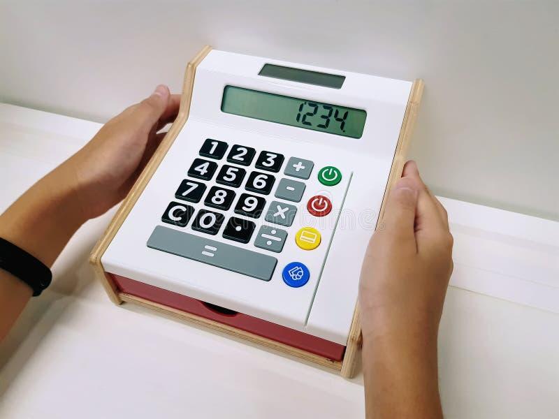 Participation de main Toy Cash Register coloré avec les boutons et l'affichage de nombre photo libre de droits