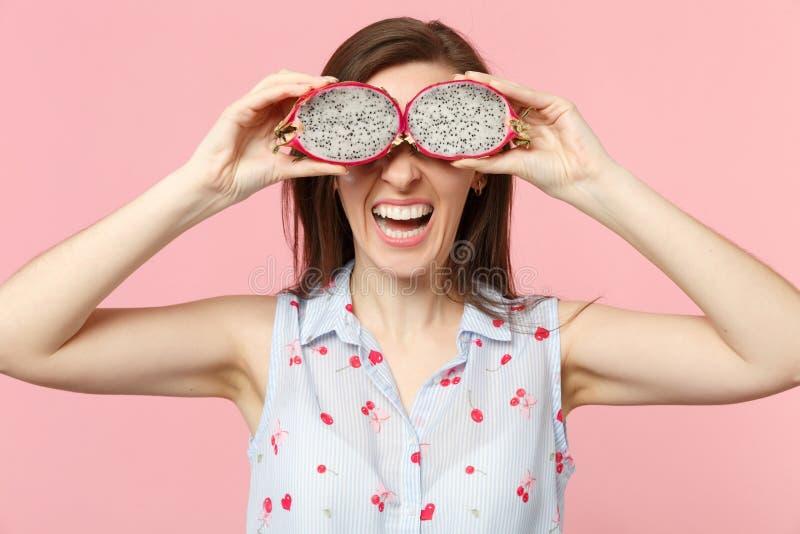 Participation riante de jeune femme, couvrant des yeux de halfs du fruit du dragon mûr frais de pitahaya d'isolement sur le mur e images libres de droits