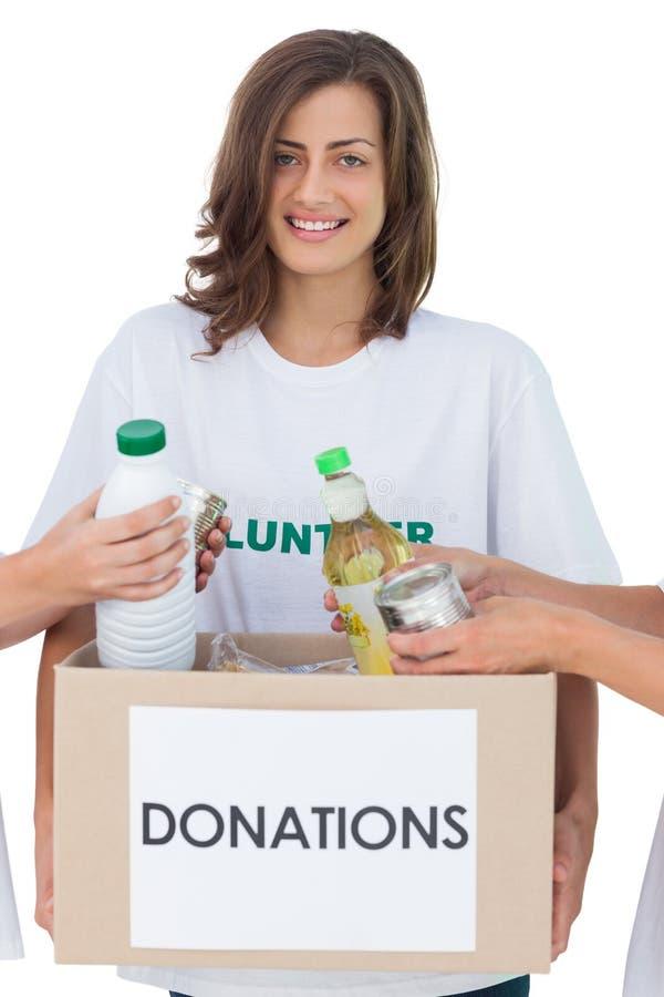 Participation volontaire de sourire une boîte de donation de nourriture photo stock