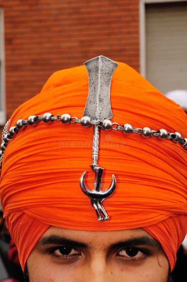 Particolare dei segni sikh sul turbante del devoto immagini stock