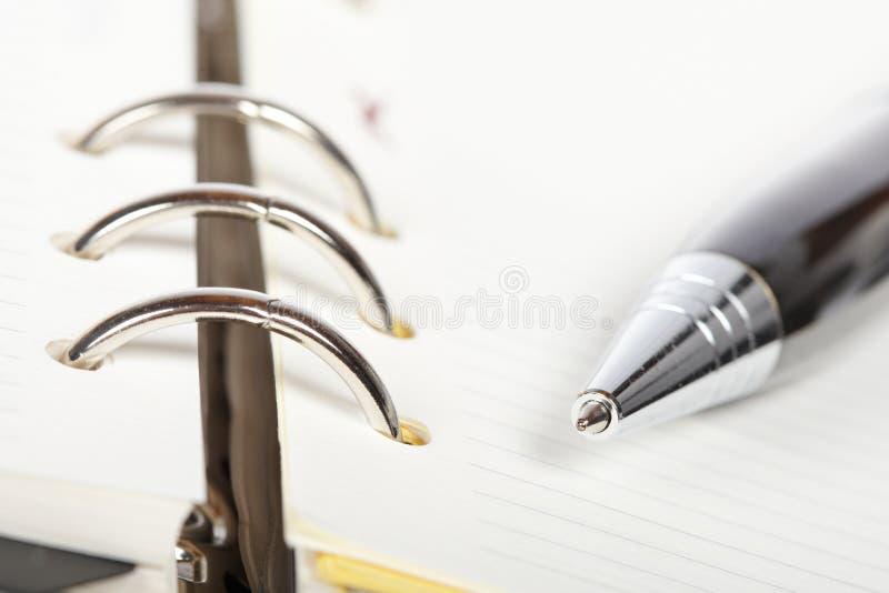 Particolare della penna e dell'ordine del giorno aperto fotografia stock