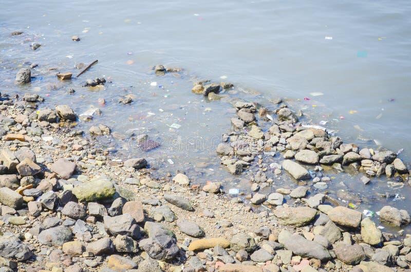Particules en plastique dissoutes microplastiques se trouvant autour sur le rivage images stock