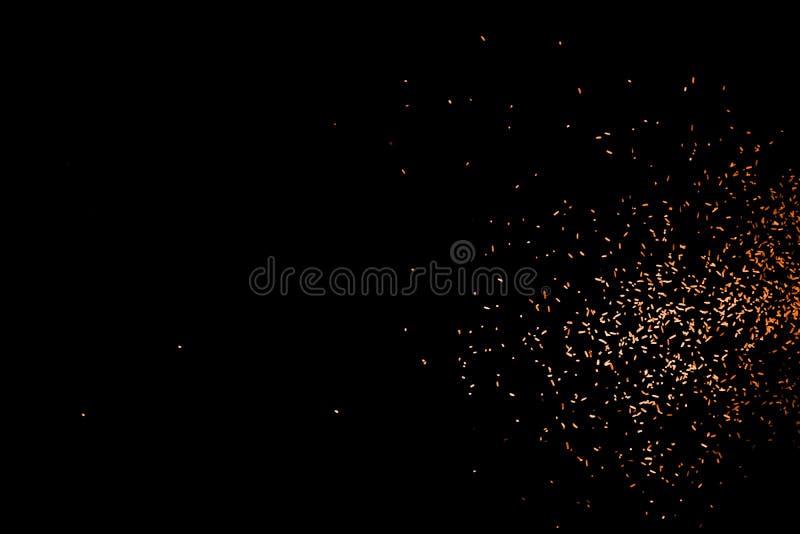 Particules oranges rouges de couleur de vol aléatoire d'isolement sur le fond noir, pour la conception abstraite recouverte images libres de droits