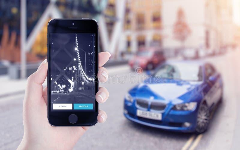 Partida da aplicação de Uber na exposição do iPhone de Apple na mão fêmea