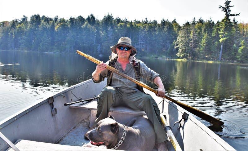 Partida del perro del hombre del barco del adirondack del lago Massawepie imagenes de archivo