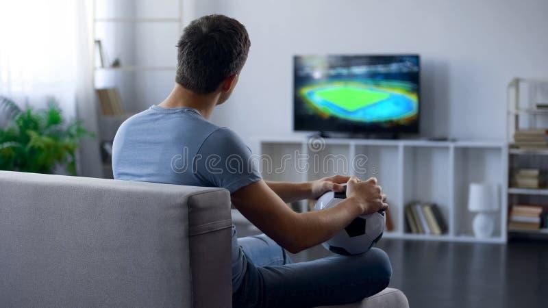 Partidario masculino del juego de observación del equipo de fútbol en casa, infeliz con resultado del partido imagenes de archivo