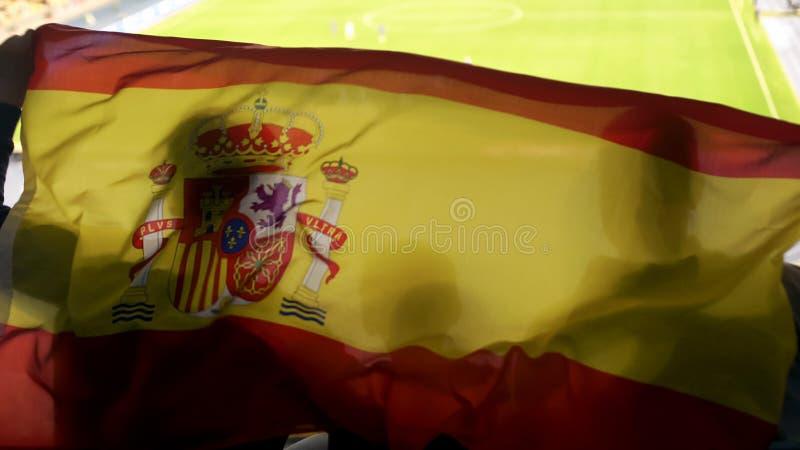 Partidarios españoles que agitan la bandera nacional, animando para la victoria del equipo de fútbol imagen de archivo libre de regalías