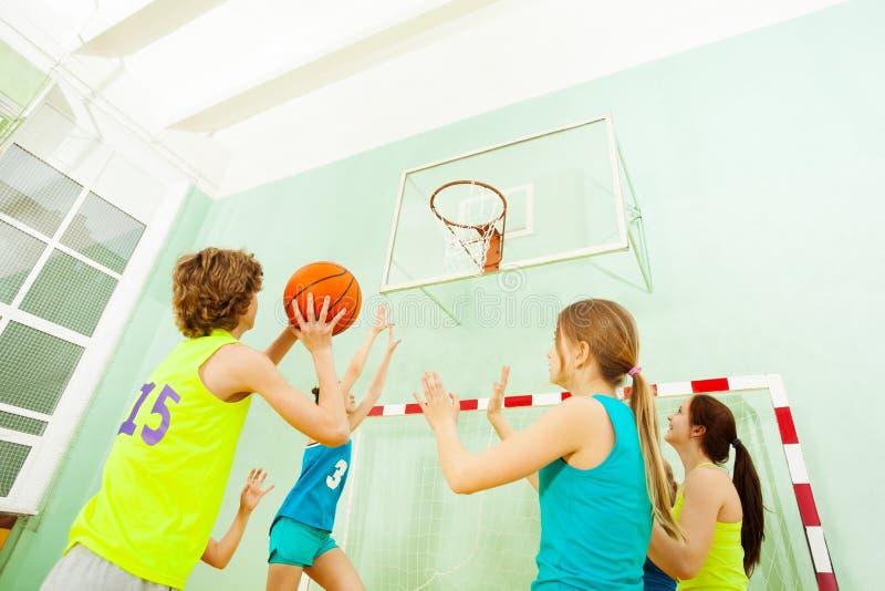 Partido de baloncesto con las muchachas que defienden contra muchacho imagen de archivo