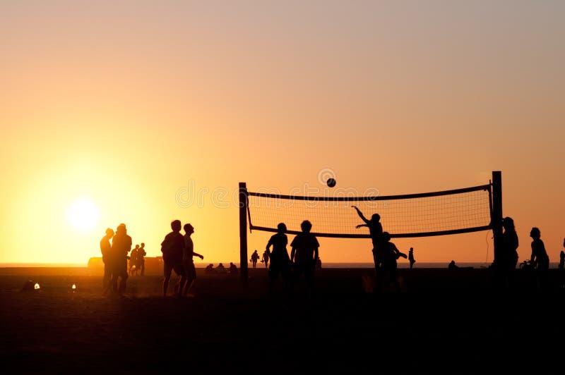 Partido de balonvolea en la puesta del sol fotos de archivo