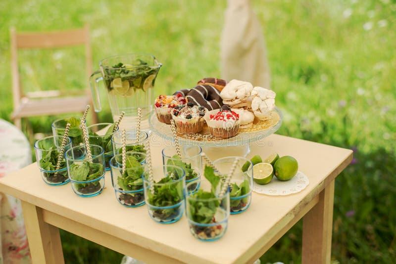Partido de coctel Tabla del postre para un partido Torta de chocolate, magdalenas, dulzor, macarrones, melcochas, céfiro y flores imagen de archivo