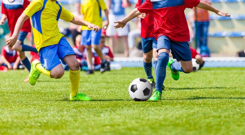Partido de fútbol del fútbol de la juventud Niños que juegan al juego de fútbol en campo de deporte imágenes de archivo libres de regalías