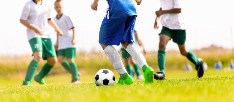 Partido de fútbol del fútbol de los muchachos en la echada imagen de archivo