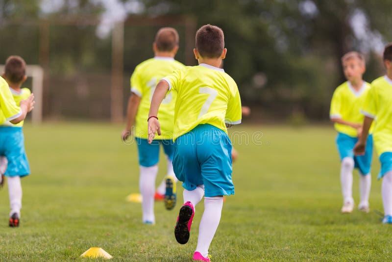 Partido de fútbol de los jugadores de los niños jovenes en campo de fútbol imagen de archivo