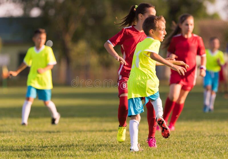 Partido de fútbol de los jugadores de los niños jovenes en campo de fútbol foto de archivo