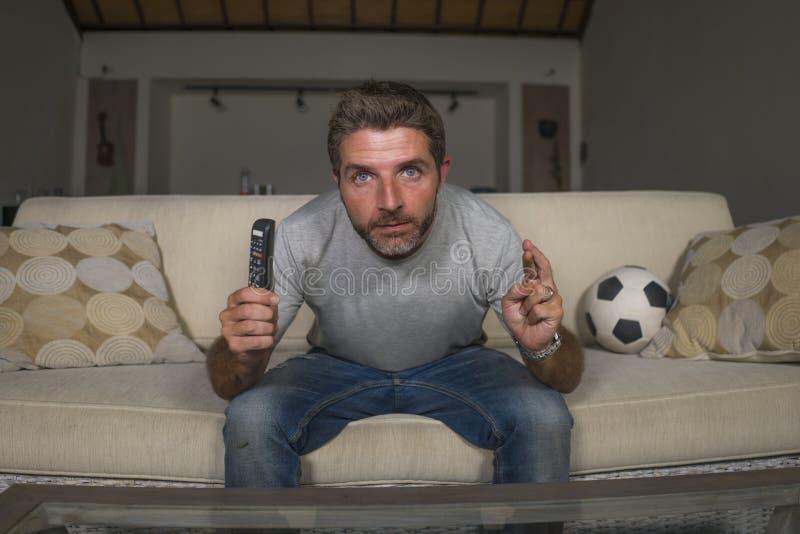 Partido de fútbol de observación atractivo del fútbol del hombre nervioso y emocionado del partidario en la televisión en la sens imagen de archivo libre de regalías