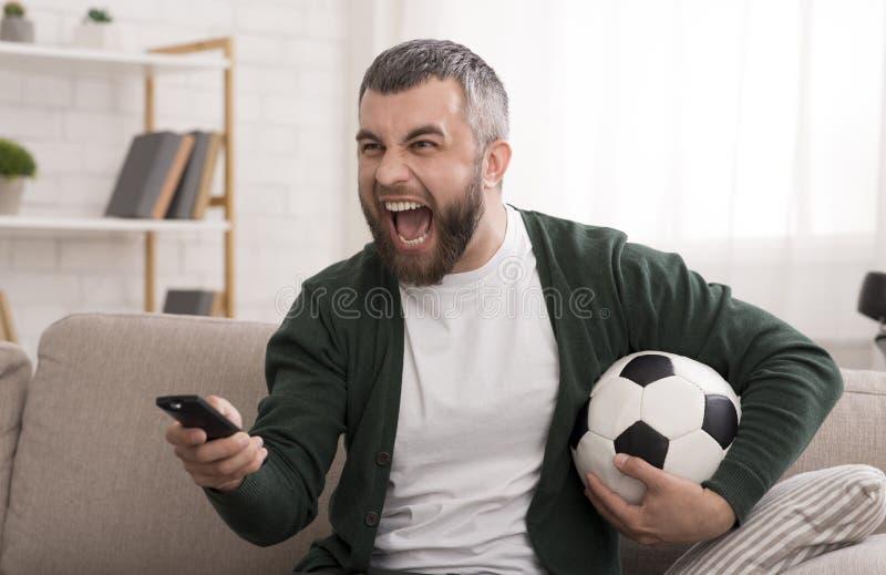 Partido de fútbol de observación del hombre caucásico enojado en la TV foto de archivo