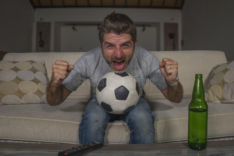 partido de fútbol de observación del hombre del fanático del fútbol 30s o 40s que celebra su griterío feliz loco de la meta del e foto de archivo