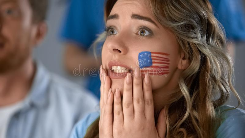 Partido de fútbol de observación del partidario femenino americano bonito en la televisión en casa fotografía de archivo