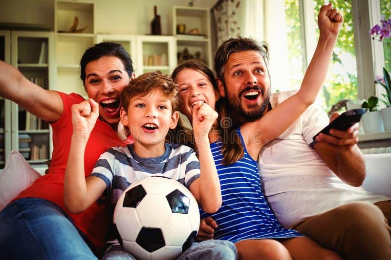 Partido de fútbol de observación de la familia emocionada foto de archivo