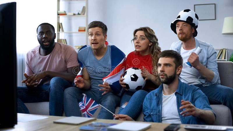 Partido de fútbol de observación de las fans británicas multiétnicas en casa, apoyando al equipo fotos de archivo libres de regalías