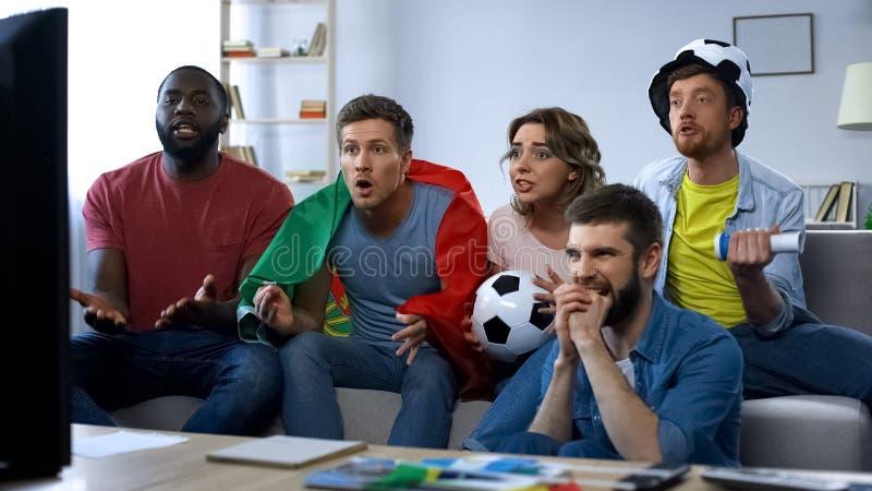 Partido de fútbol de observación de los amigos multiétnicos de Portugal en casa, apoyando al equipo imagen de archivo libre de regalías