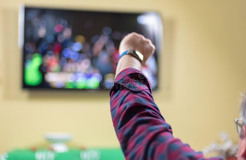 Partido de fútbol de observación que anima del hombre en la TV fotografía de archivo libre de regalías